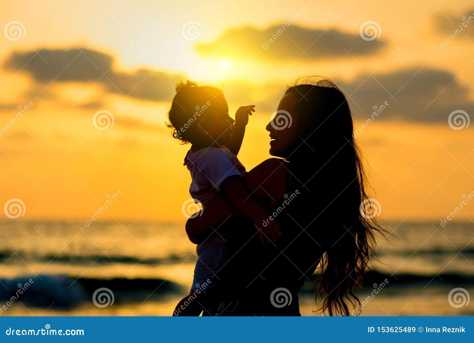 Ung moder för konturer med dottern som spelar och ler på stranden på solnedgången Lyckligt familj- och loppbegrepp