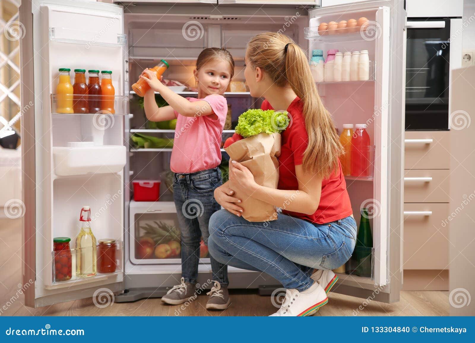Ung moder med dottern som sätter mat in i kylskåpet