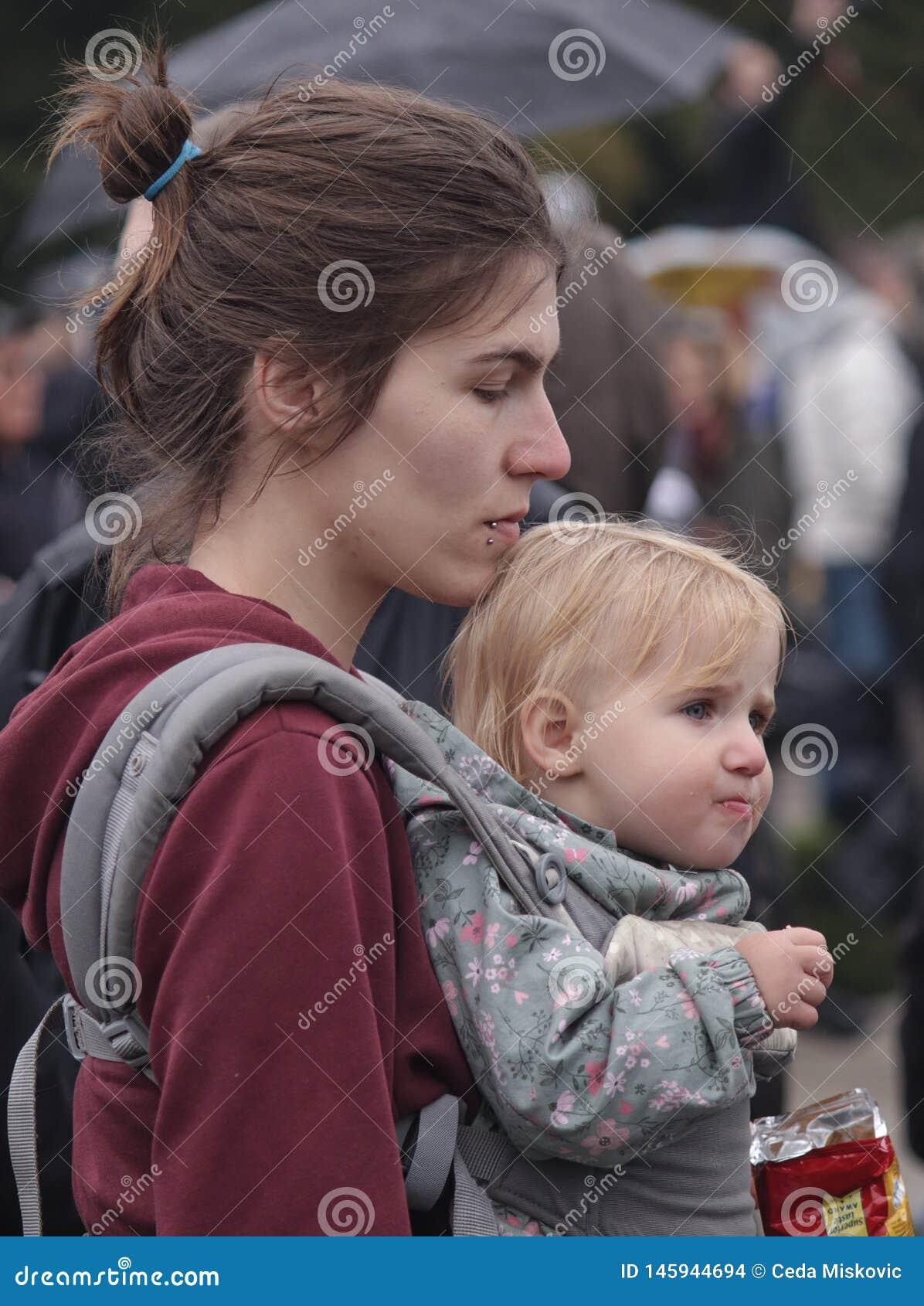 Ung moder och hennes barn på protesten