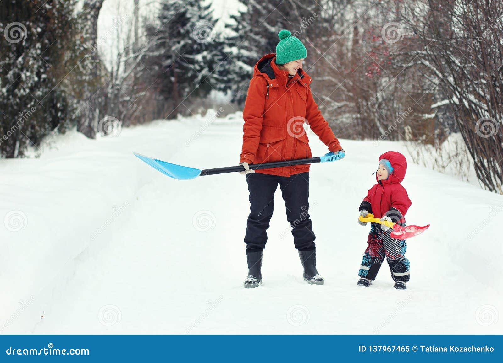 Ung moder och hennes litet barnsonställning med snöskyfflar på den lantliga vägen Säsongsbetonat begrepp för vinter