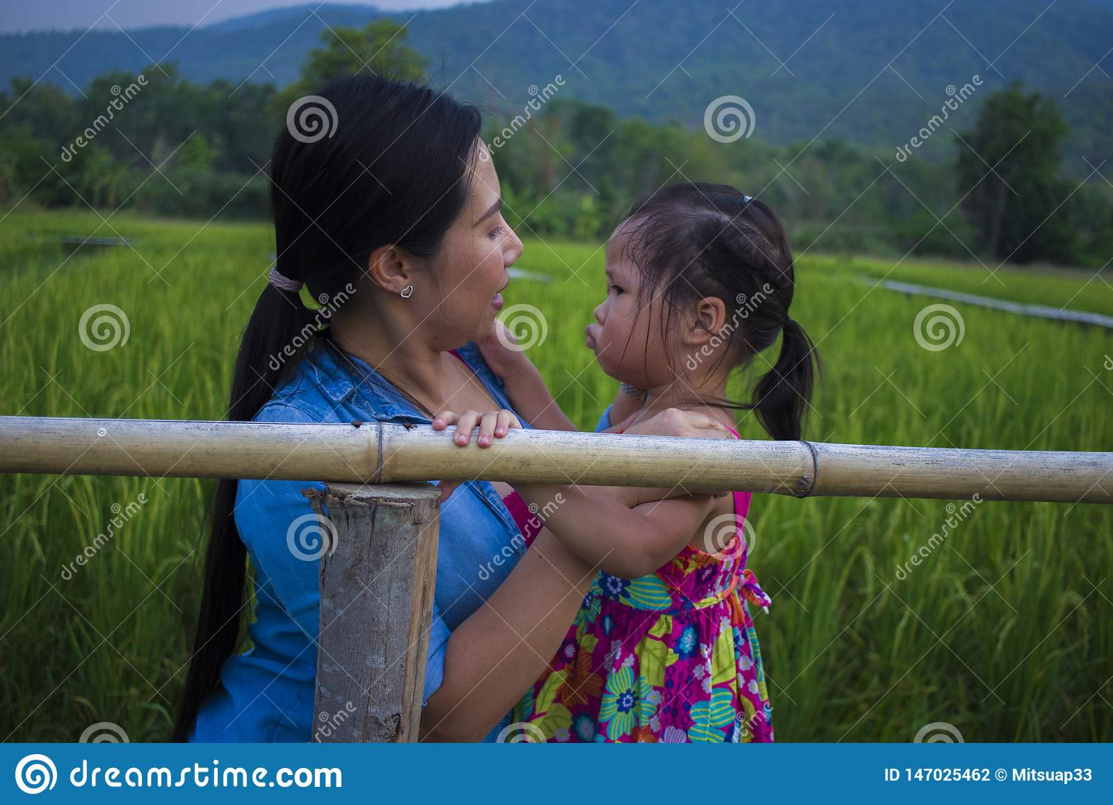 Ung moder som kramar och lugnar en skriande liten dotter, en asiatisk moder som f?rs?ker att tr?sta och lugna ner hennes skriande