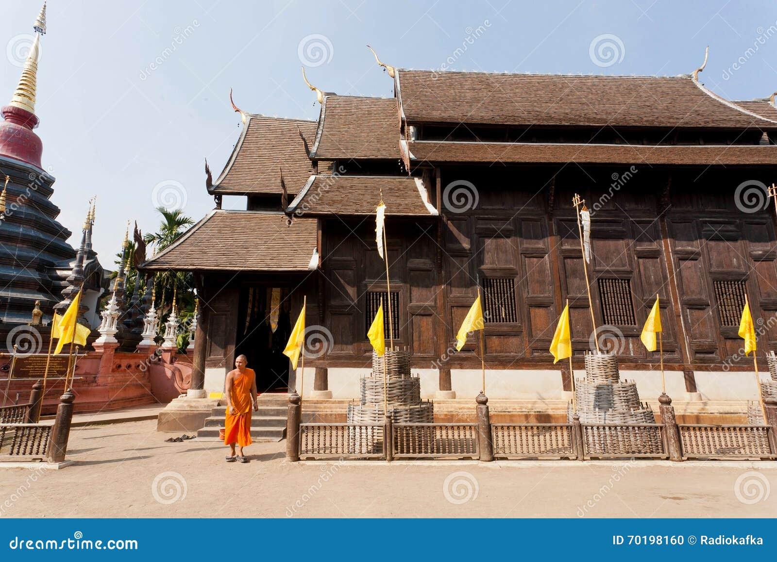 Ung munk i gul klänning som går från trätemplet som byggs i det 14th århundradet