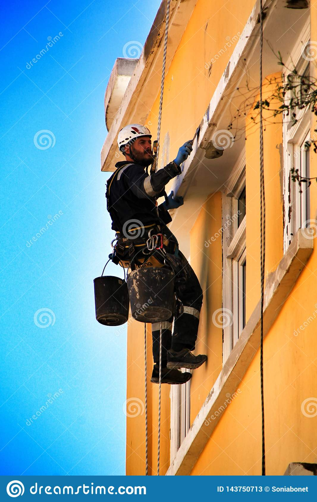 Ung murarekl?ttrare som g?r reparationsarbete i en fasad av Lissabon