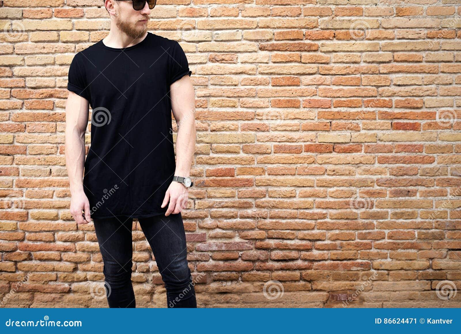 Ung muskulös man som bär den svarta tshirten, solglasögon och jeans som utanför poserar Töm den bruna grungetegelstenväggen på