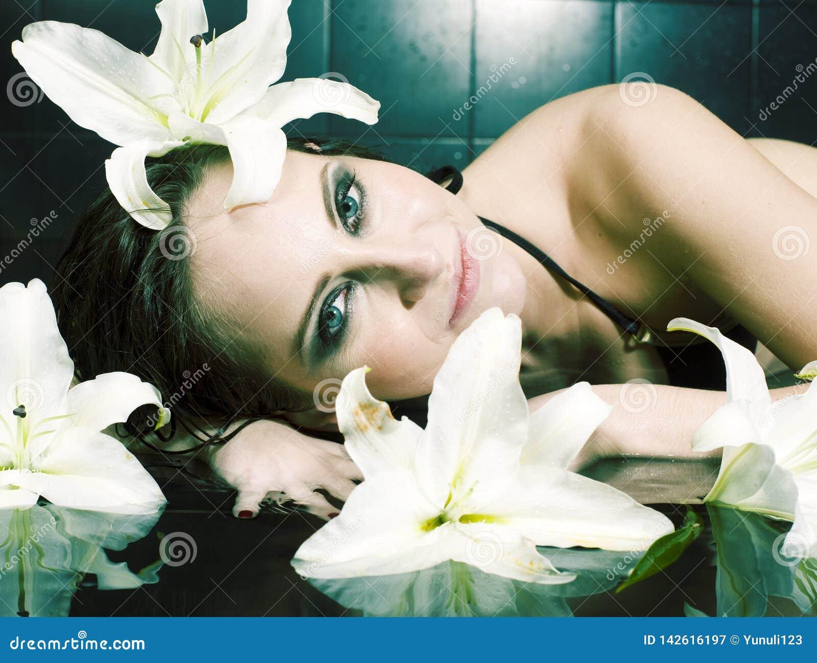 Ung nätt brunettkvinna i det svarta badet som tar brunnsortomsorg som poserar med liljan för vit blomma