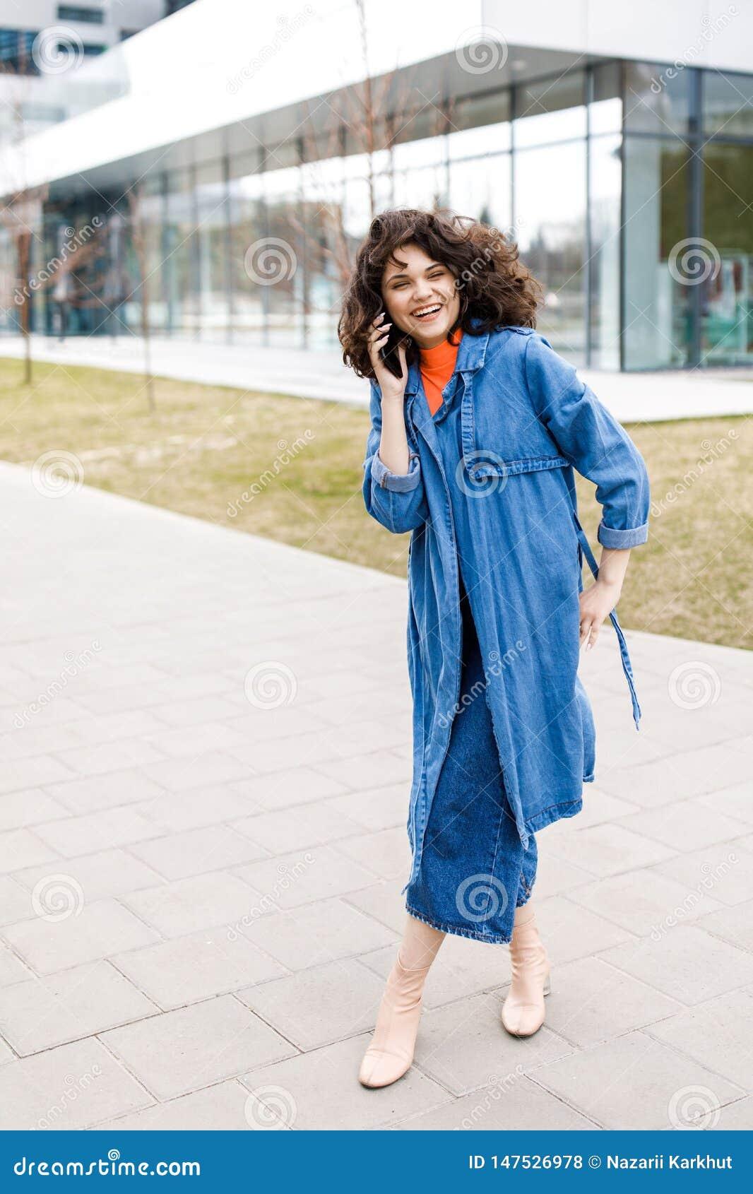 Ung nätt flicka som går på gatan, den iklädda jeansen och grov bomullstvillskjortan Studentvardagar Flickan talar på gatan på