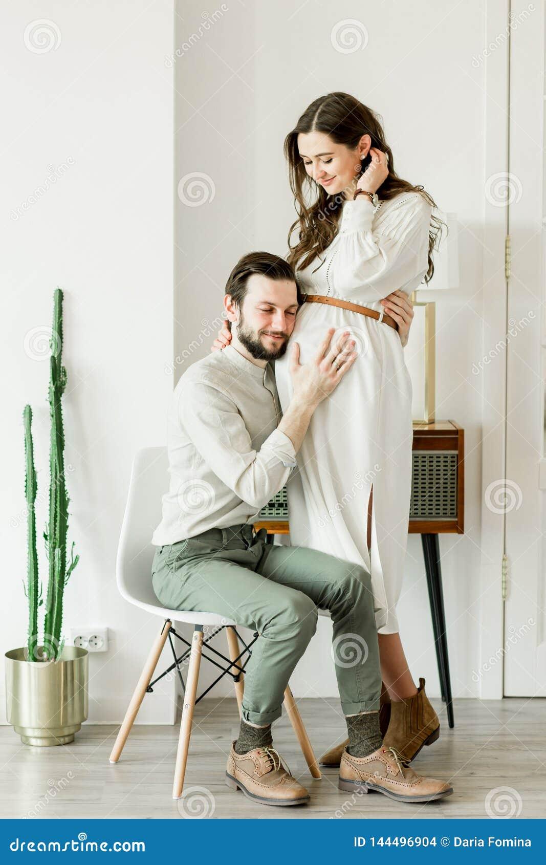 Ung nätt gravid kvinna och hennes make i hattanseende nära kaktusväggen
