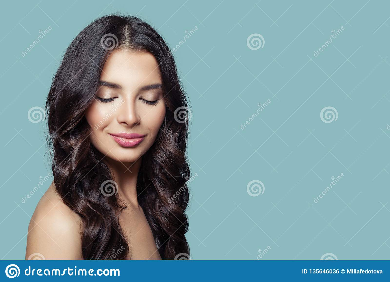 Ung nätt kvinna med långt sunt hår och naturlig makeup på blå bakgrund