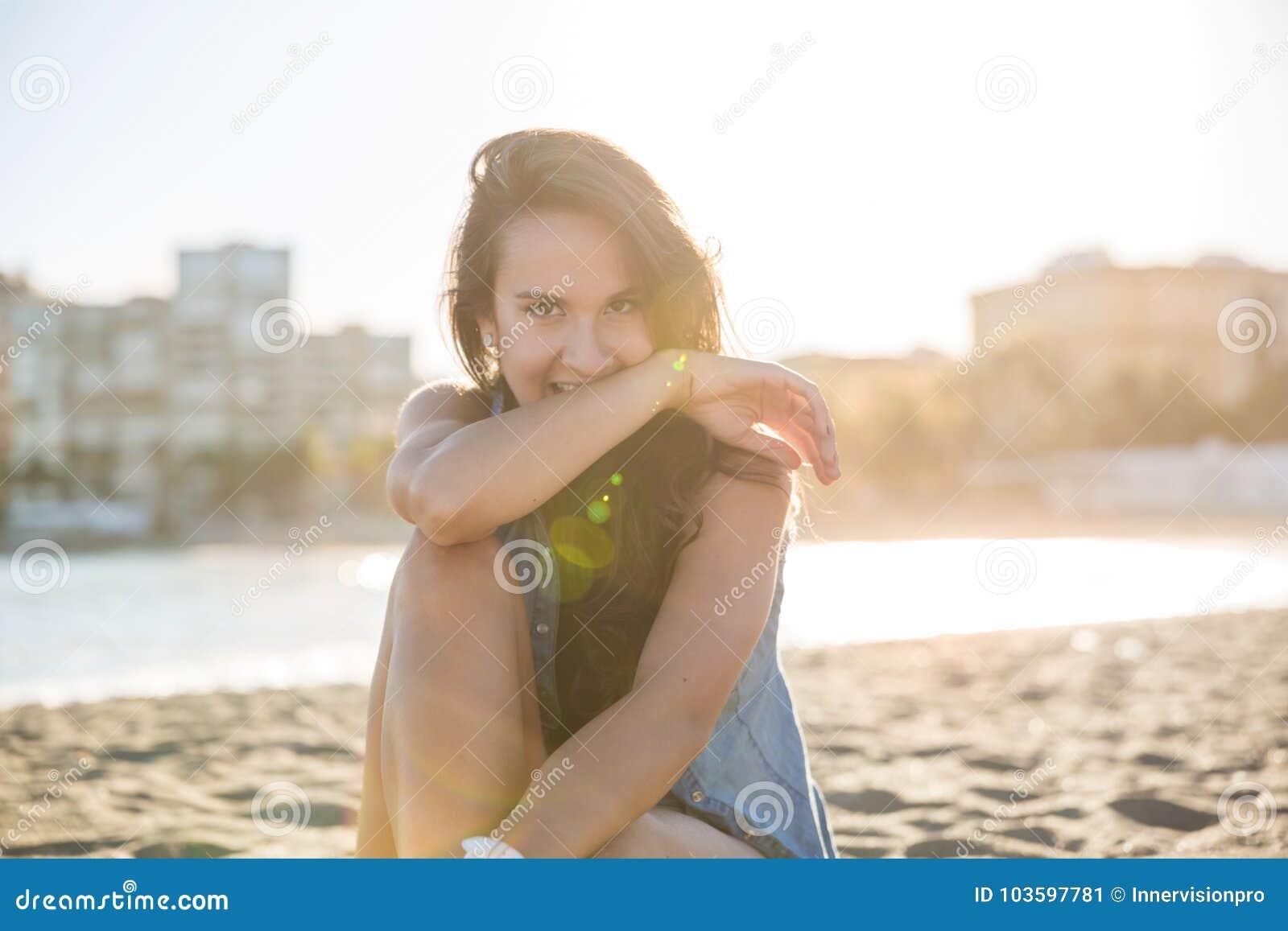 Ung nätt kvinna på stranden som ser tänka bort