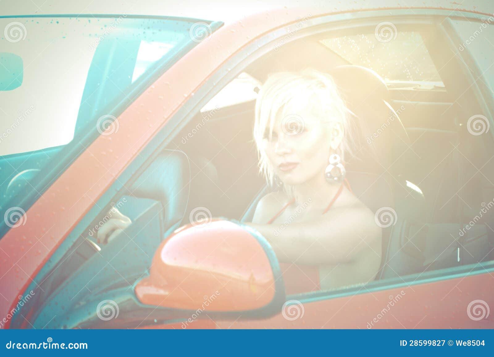 Ung nätt kvinna som chauffören av den röda sportbilen