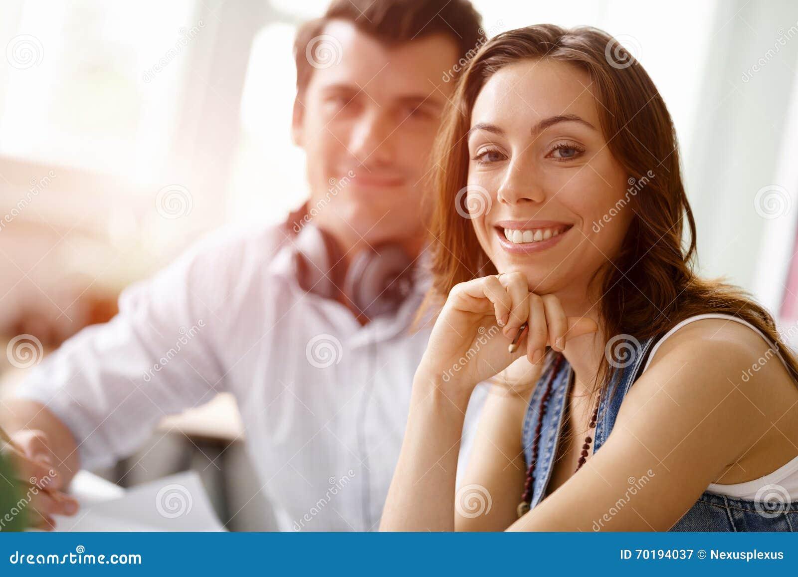 Ung nätt kvinna som ler med mannen på bakgrund