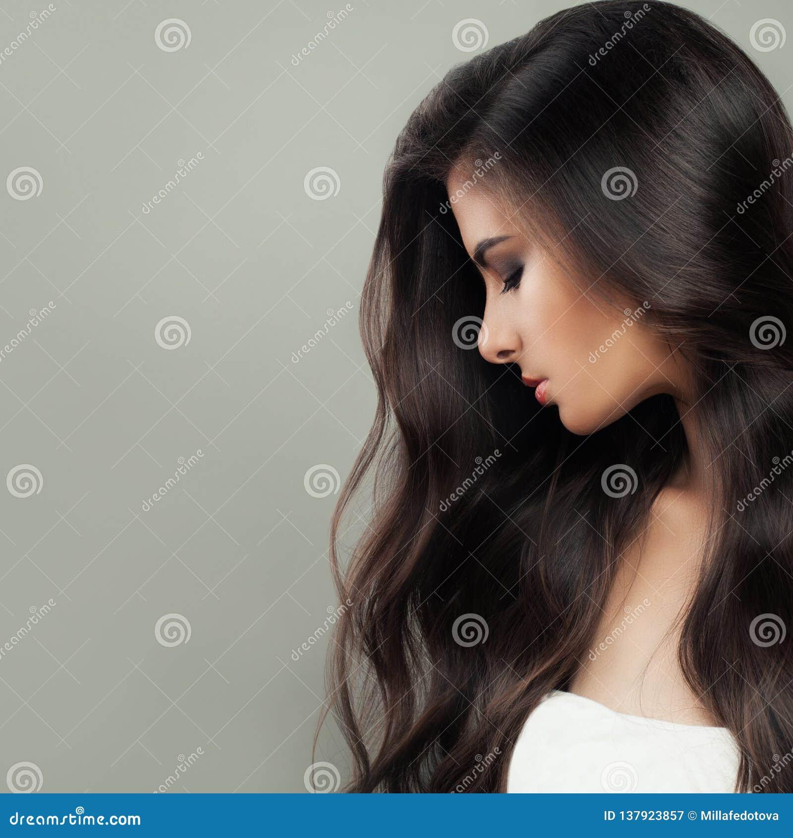 Ung perfekt brunettkvinnastående Långt mörkt sunt hår och naturlig makeup Begrepp för håromsorg