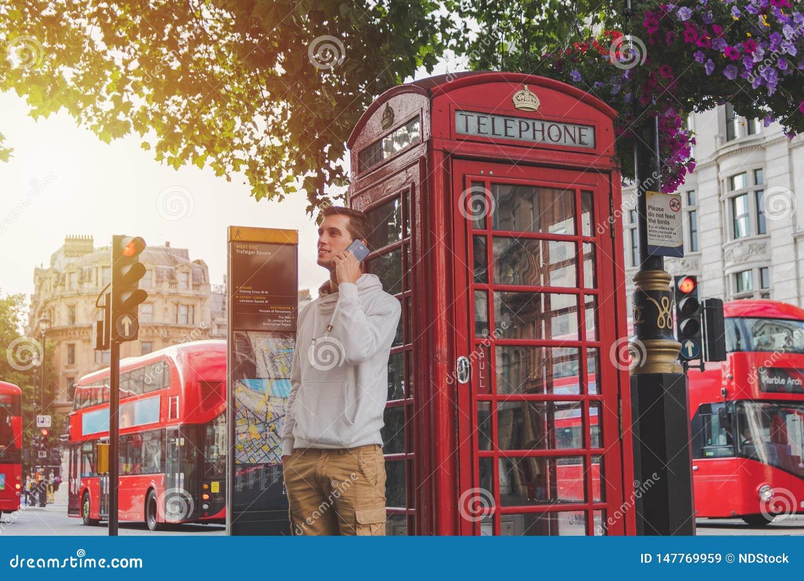 Ung pojke som framme använder smartphonen av en telefonask och en röd buss i London