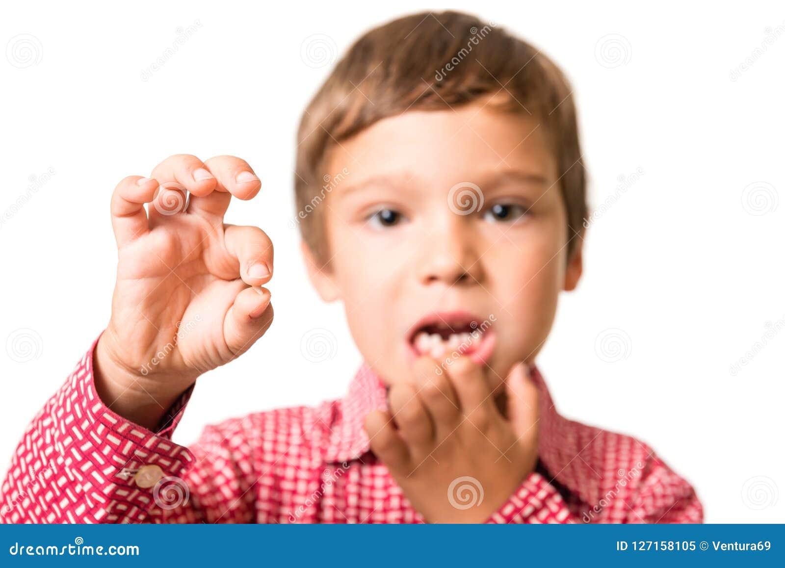 Ung pojke som visar hans första borttappade mjölka-tand
