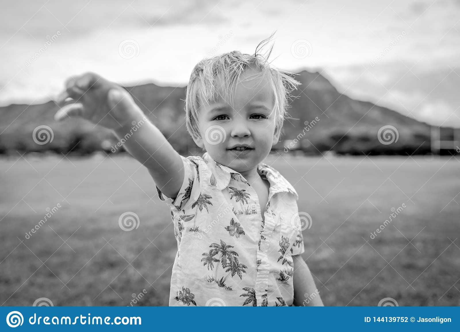 Ung pojke stående bärande Aloha Shirt i fält