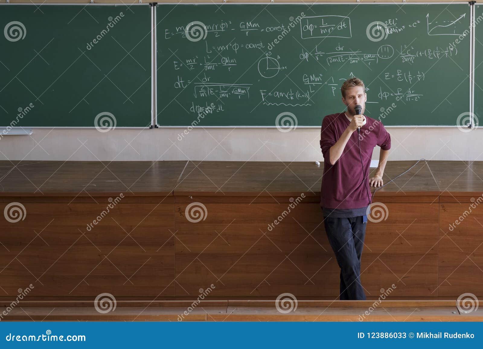 Ung professorföreläsare med talande och undervisande studenter för mikrofon i stor hörsal