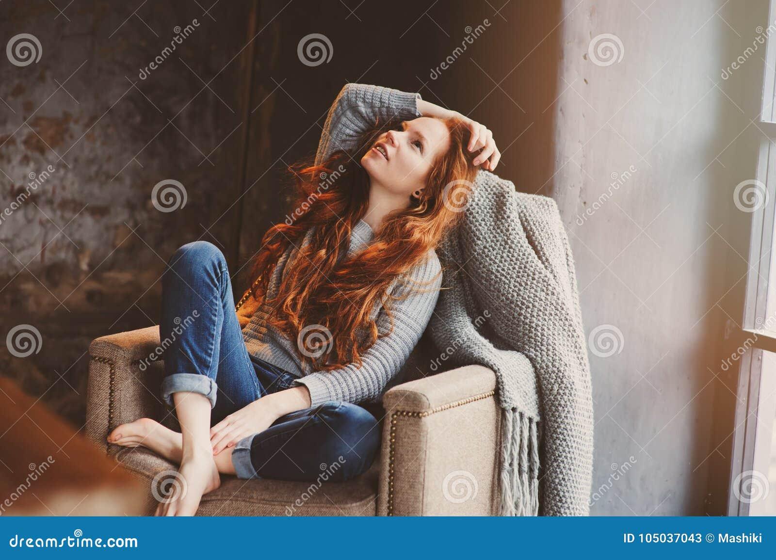 Ung readheadkvinna som hemma kopplar av i hemtrevlig stol, iklädd tillfällig tröja och jeans