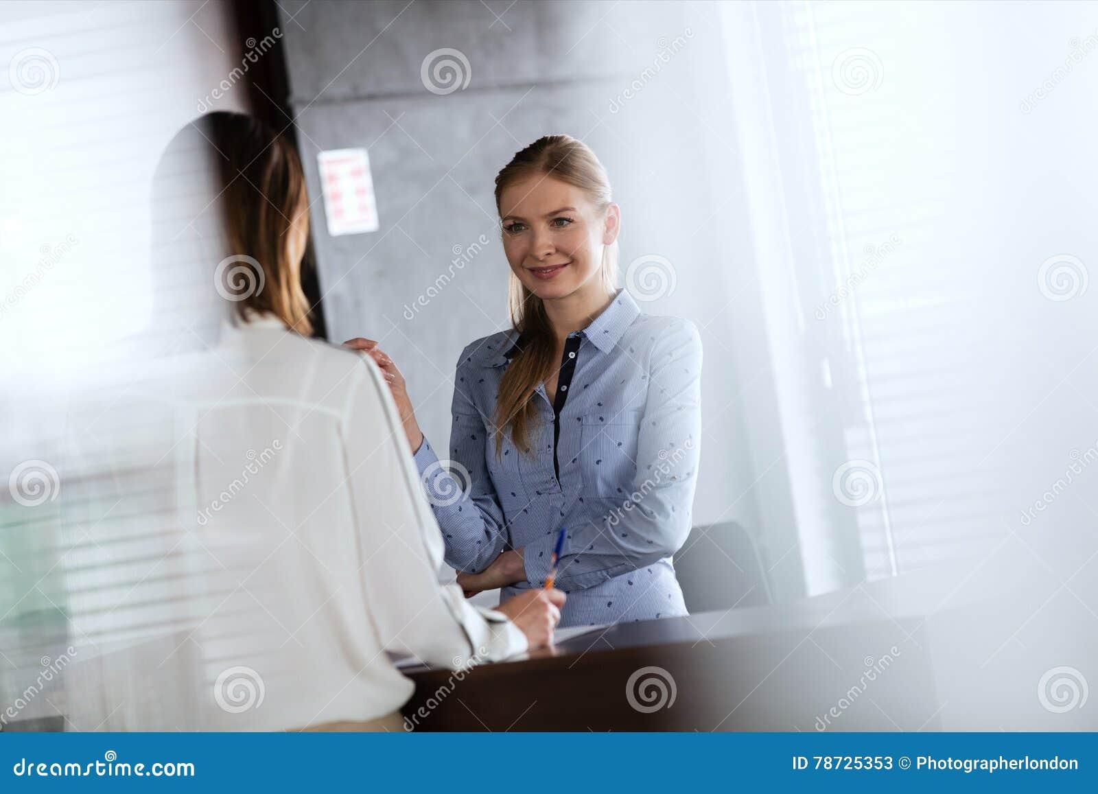 Ung receptionist som i regeringsställning talar med affärskvinnan