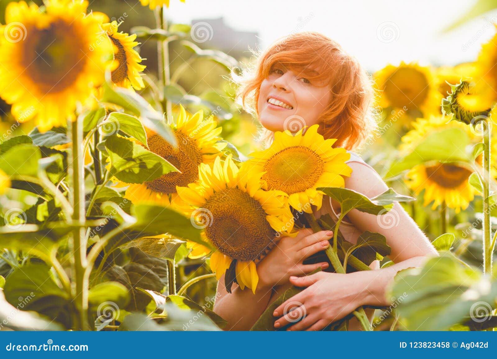 Ung redheaded kvinna i fältet av solrosor som rymmer en enorm grupp av blommor i en solig sommarafton