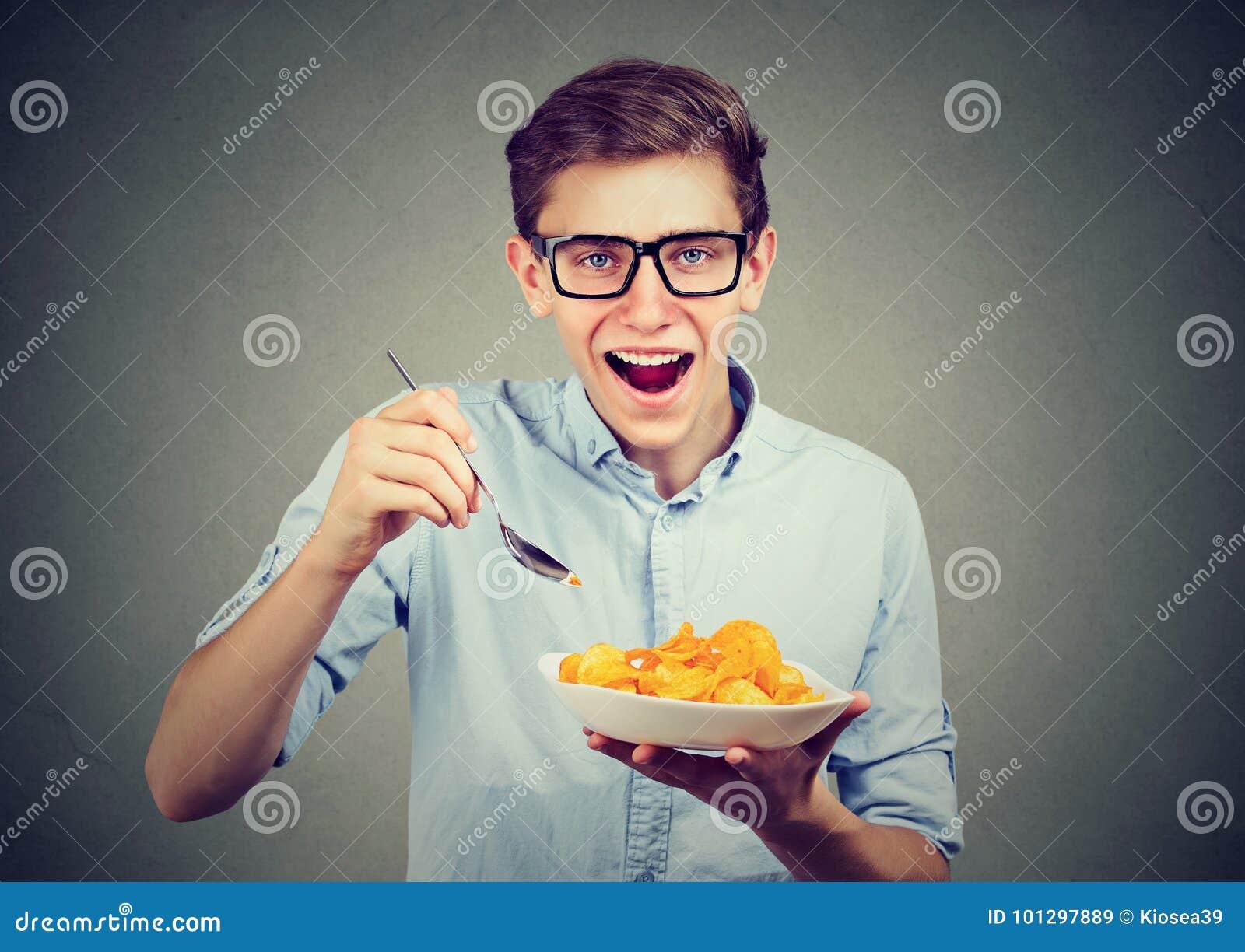 Ung rolig man som har en platta av potatischiper