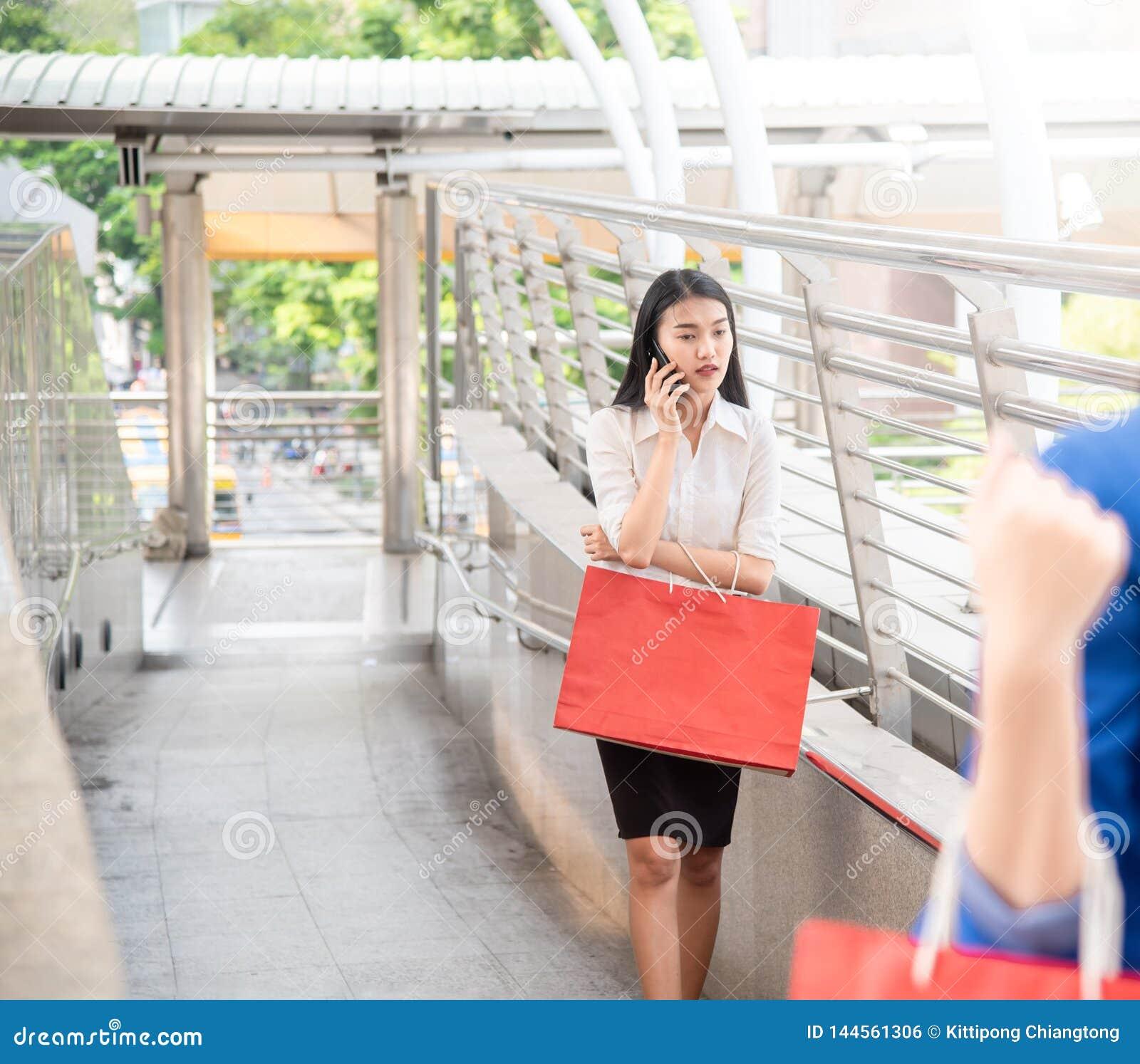 Ung säker asiatisk affärskvinna som talar på mobiltelefonen med färgrika shoppa påsar som går på shoppinggallerian i stade