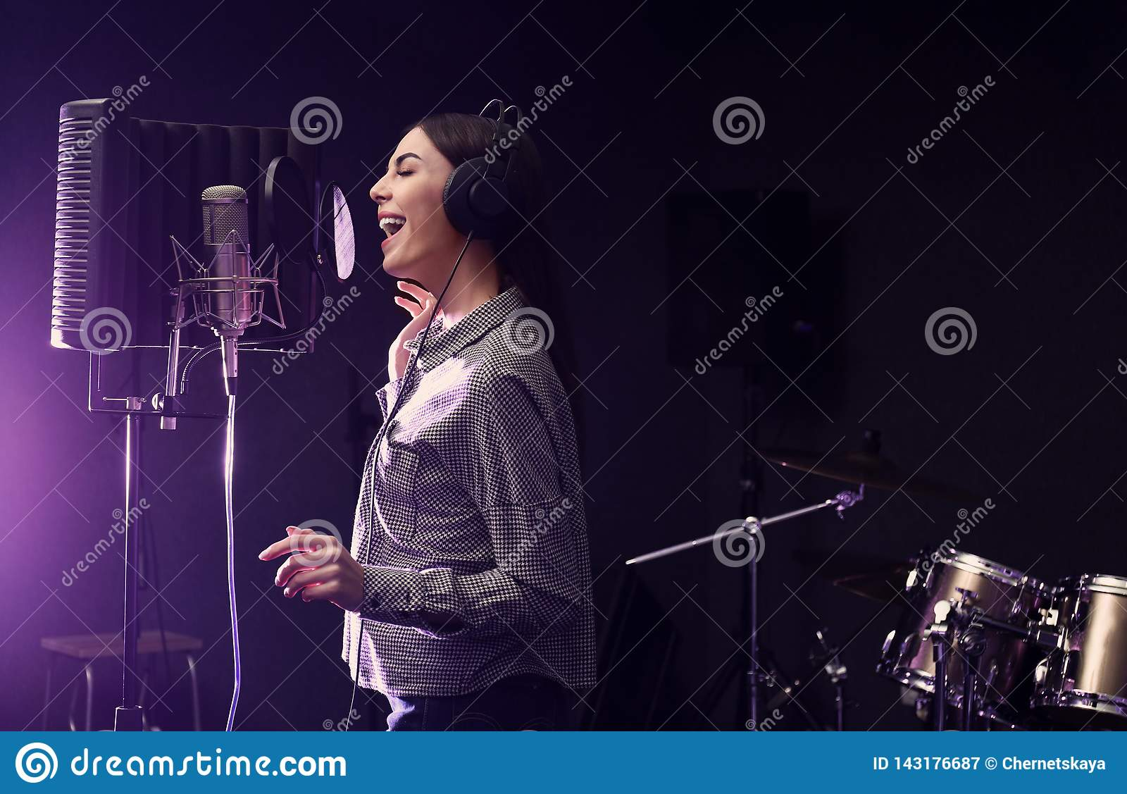 Ung sångare med mikrofoninspelningsång i studio