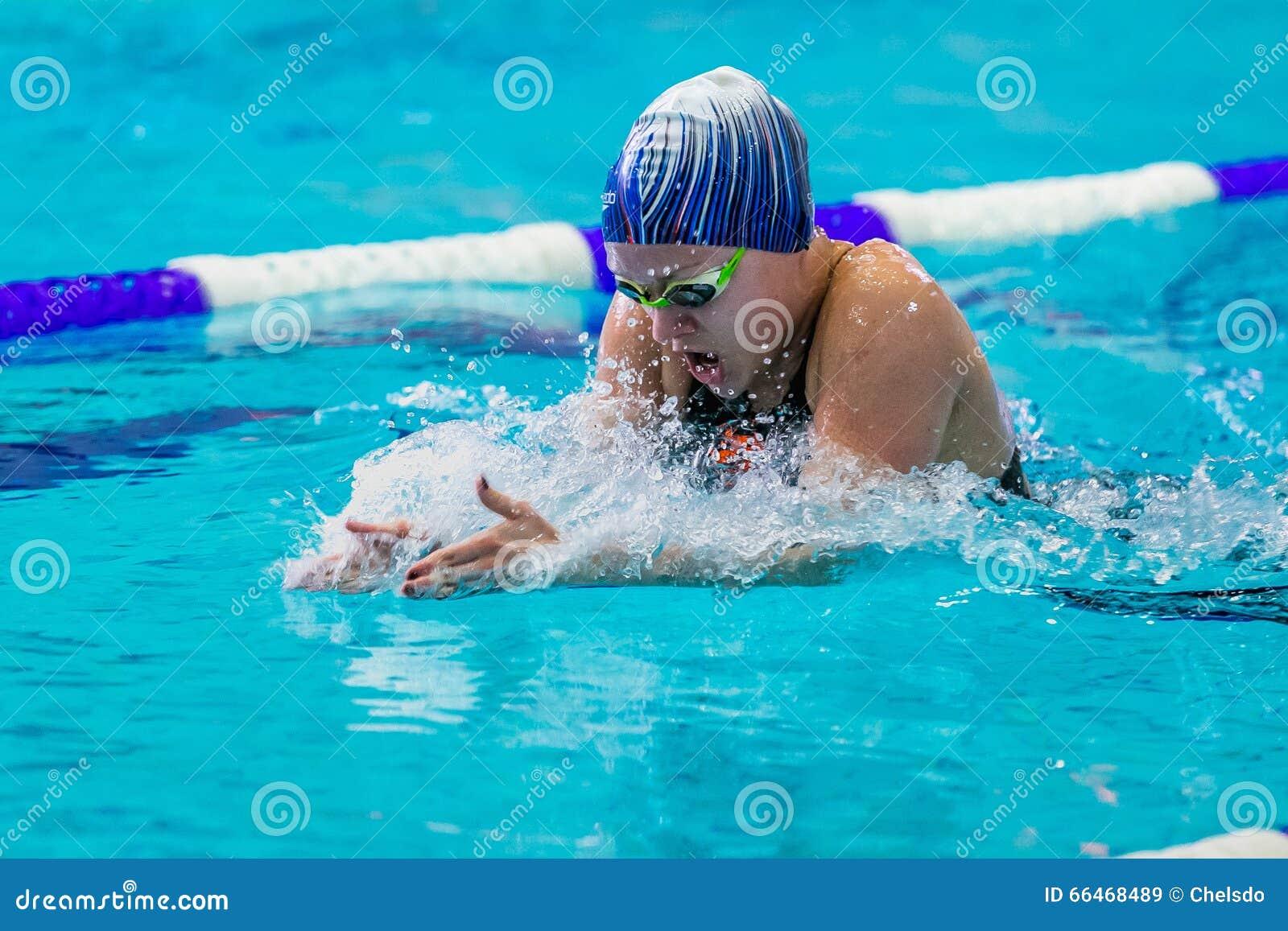 Ung simningbröstsim för kvinnlig idrottsman nen i pöl