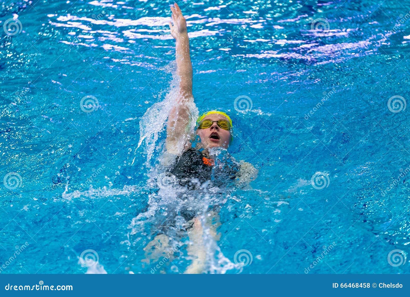 Ung simningryggsim för kvinnlig idrottsman nen sprintar in avstånd i pöl