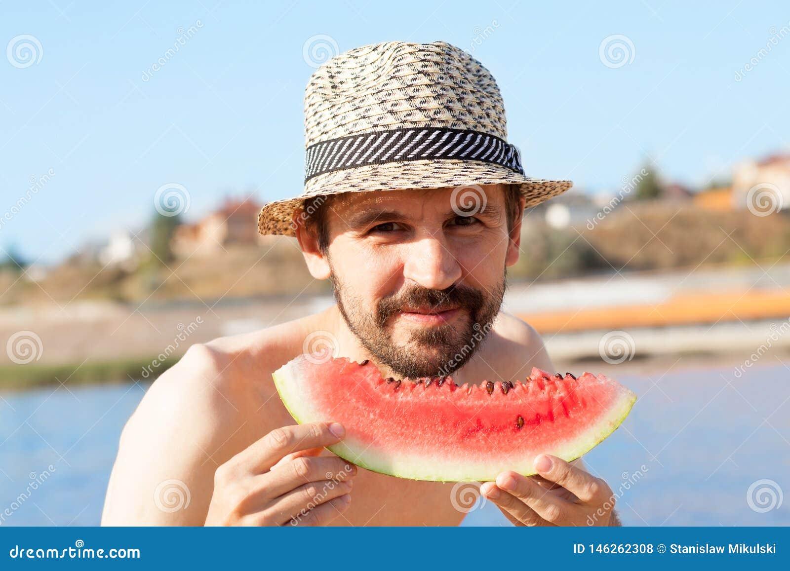 Ung skäggig man med en vattenmelon på stranden