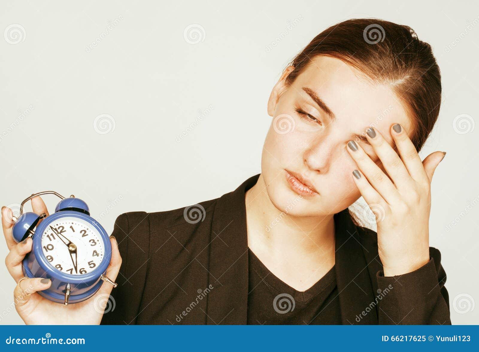Ung skönhetkvinna i affärsstildräkten som vaknar upp för arbetsotta på vit bakgrund med att dricka för klocka