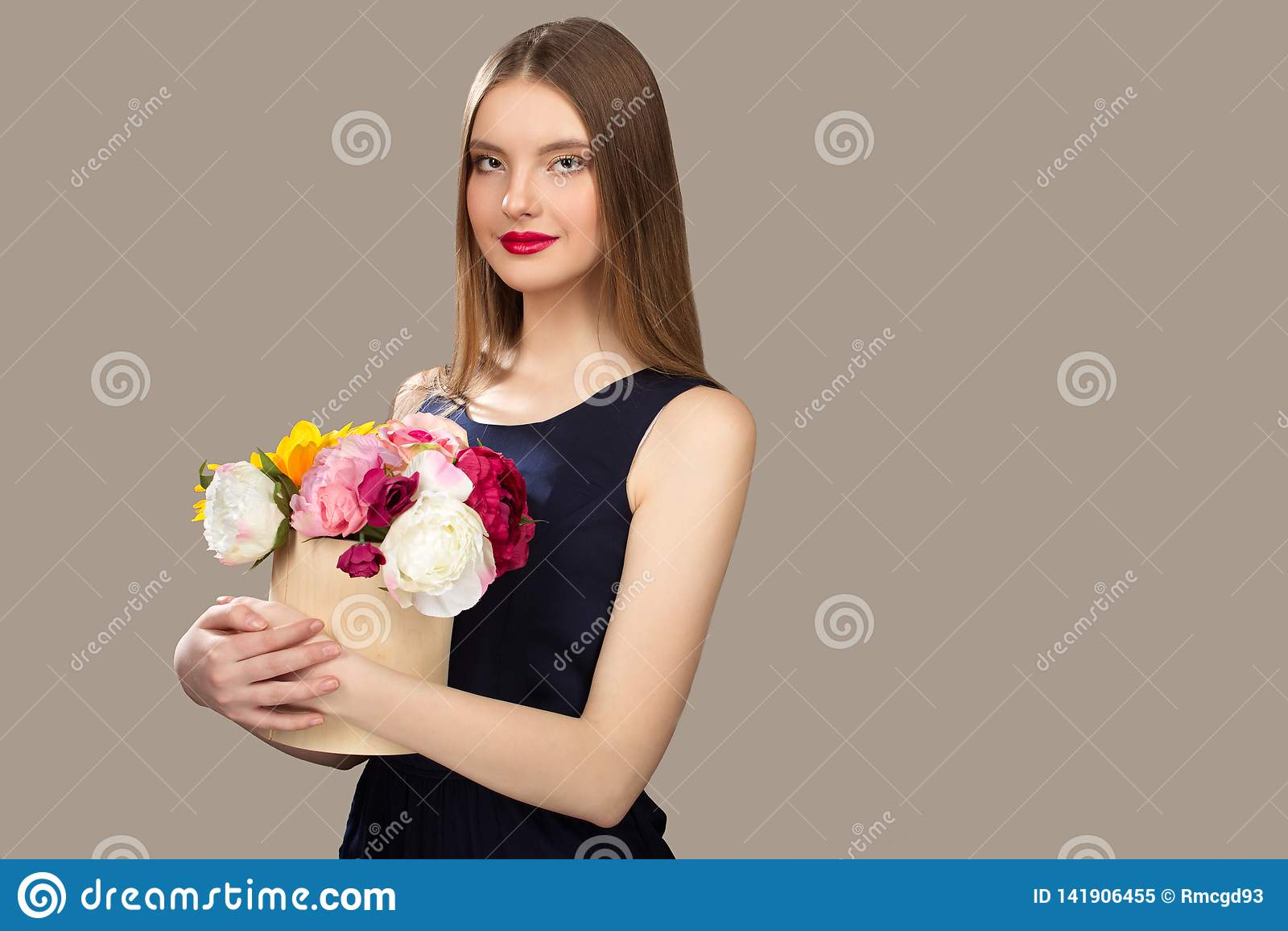 Ung skönhetkvinna som rymmer blommor i hennes händer