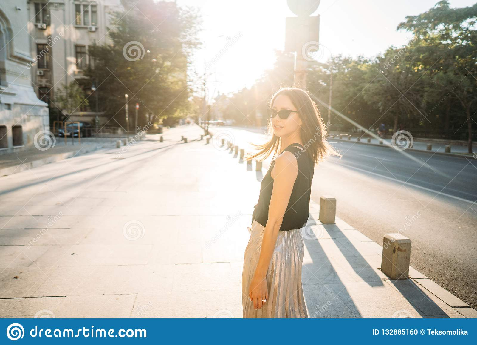 Ung stilfull hipsterkvinna som går på gatan