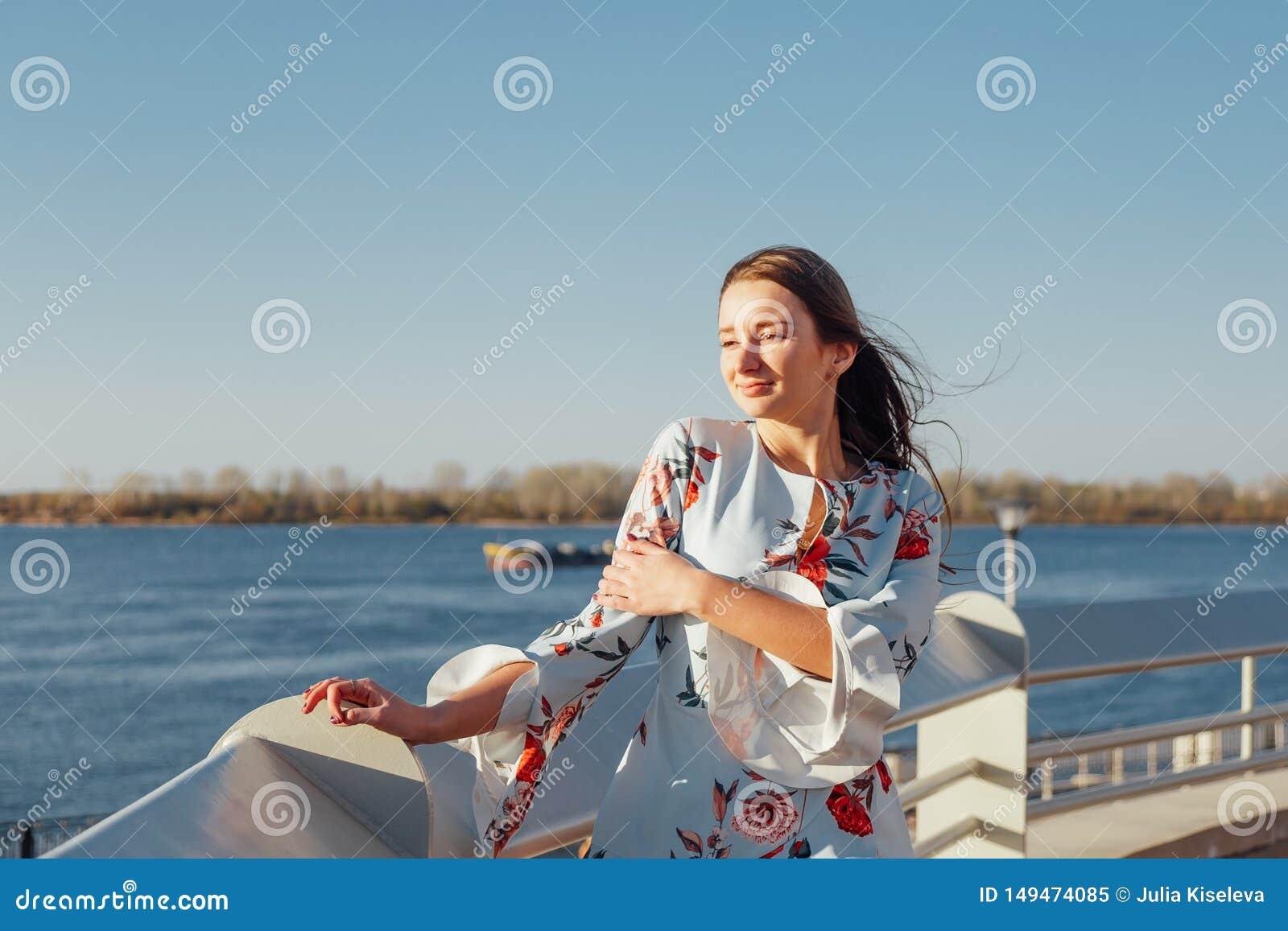 Ung stilfull kvinna, i delikat bl?tt kl?nninganseende p? stranden och att tycka om solnedg?ngen