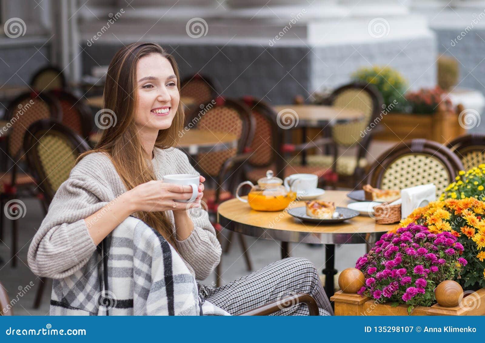 Ung stilfull kvinna som har en fransk frukost med kaffe och kakan som sitter på kaféterrassen