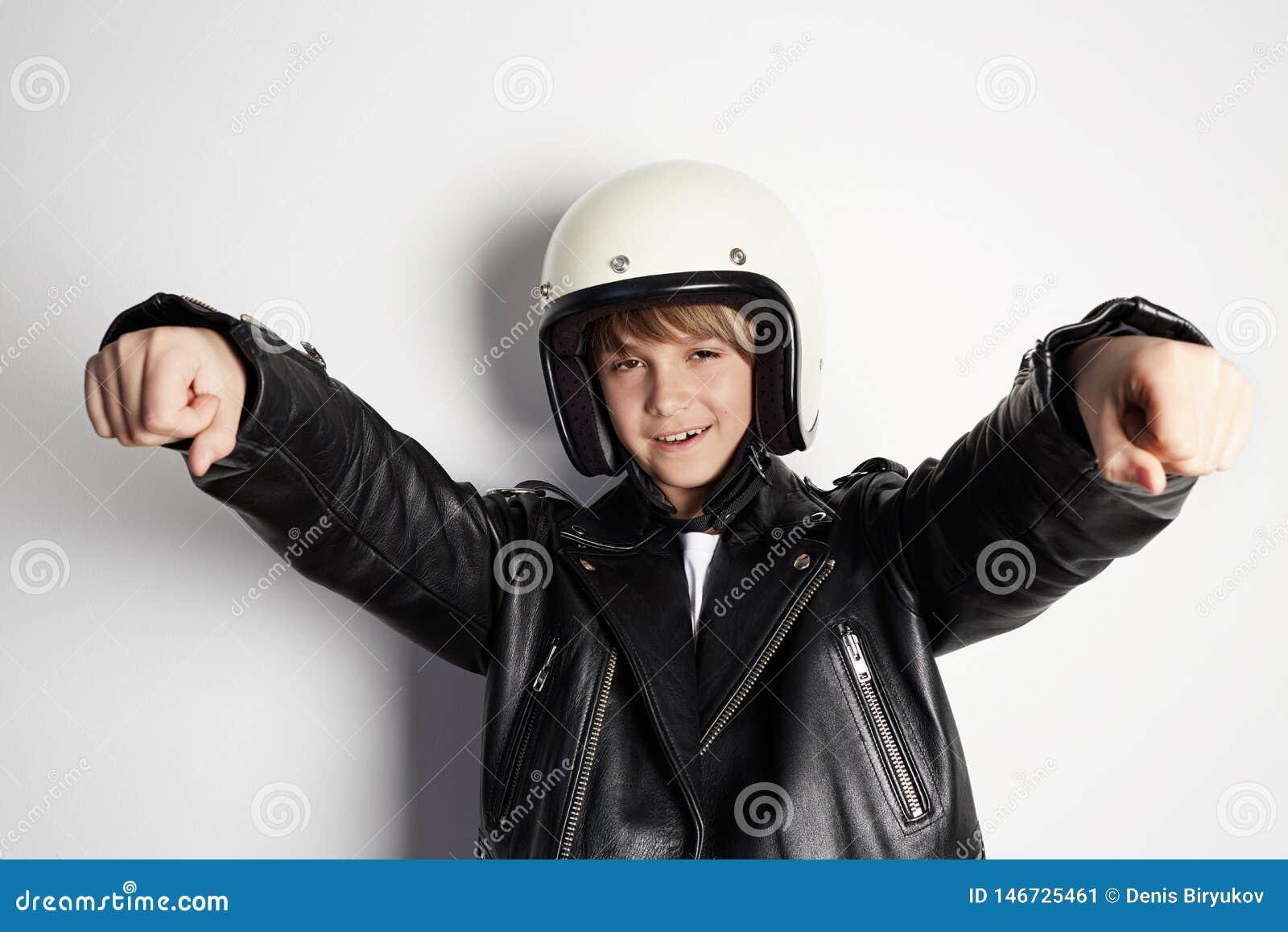 Ung stilfull ungepojke i svart läderomslag och den vita motohjälmen som låtsar för att rida en motorcykel över på vit