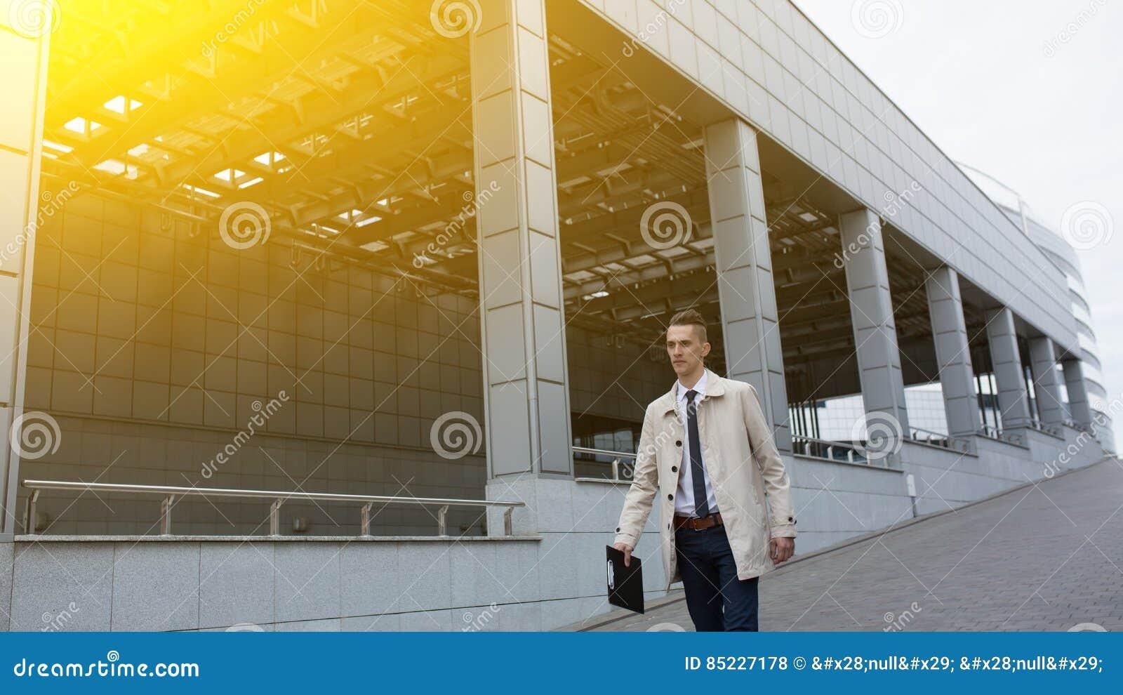 Ung stilig affärsman som går i finansiellt område