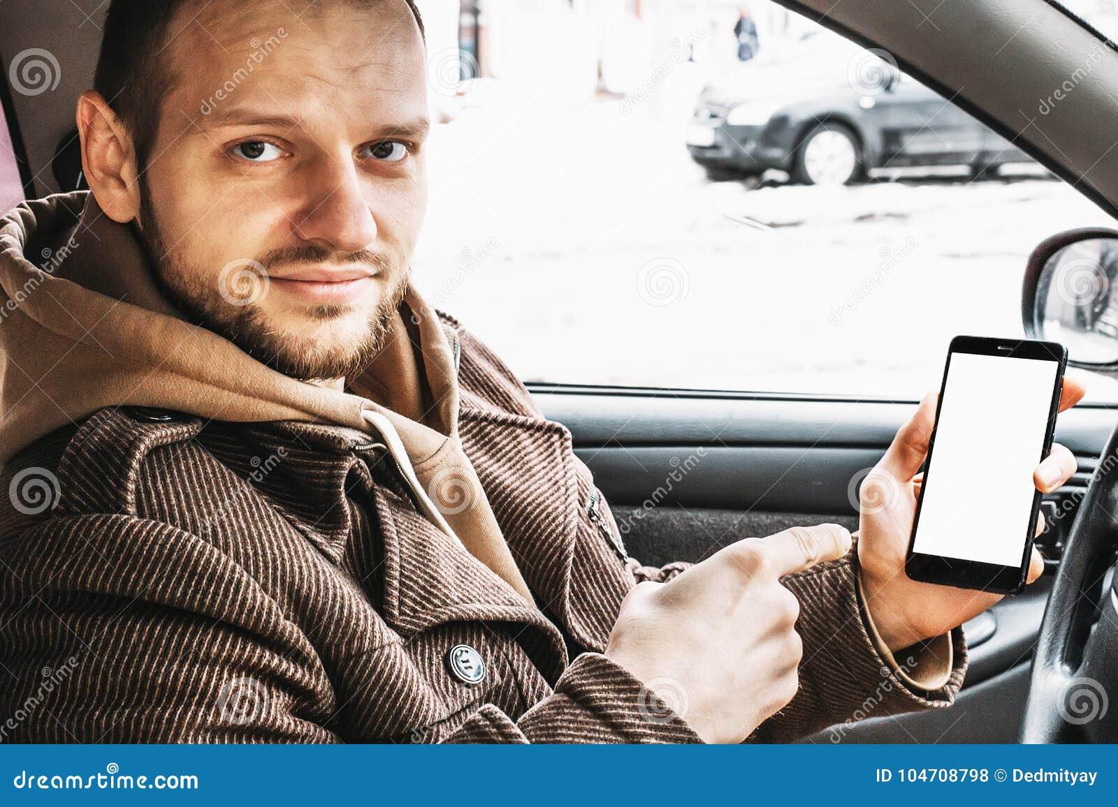 Ung stilig le manvisningsmartphone eller vit skärm för mobiltelefon som åtlöje upp för ditt produktsammanträde i bil