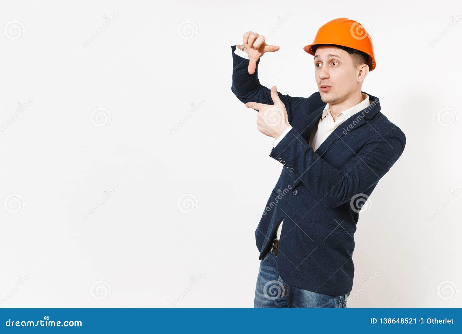 Ung stilig lyckad affärsman i den mörka dräkten, skyddande konstruktionshjälm som gör gest för handfotoram