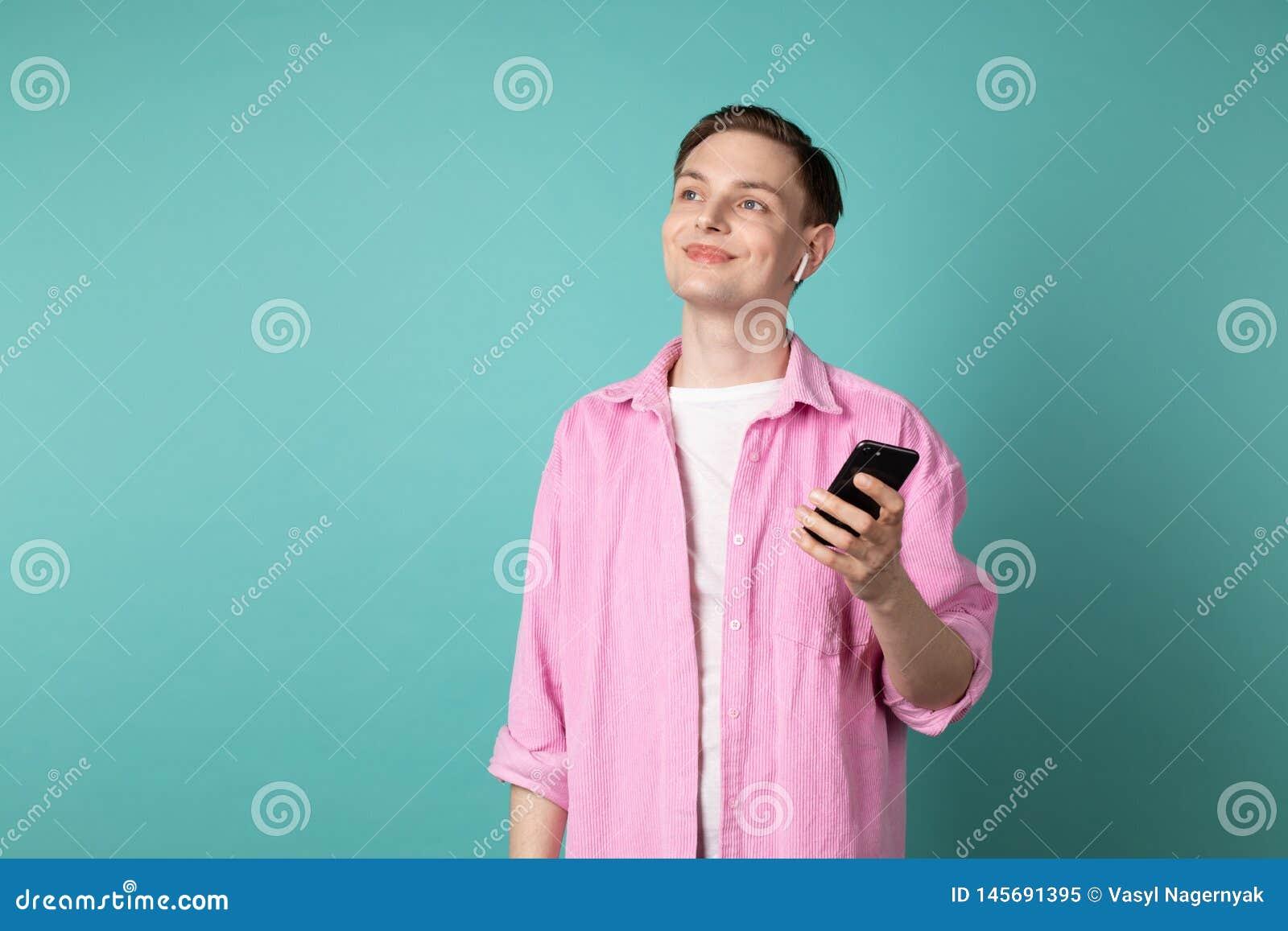 Ung stilig man i rosa skjorta med telefonen i h?nder och vita h?rlurar