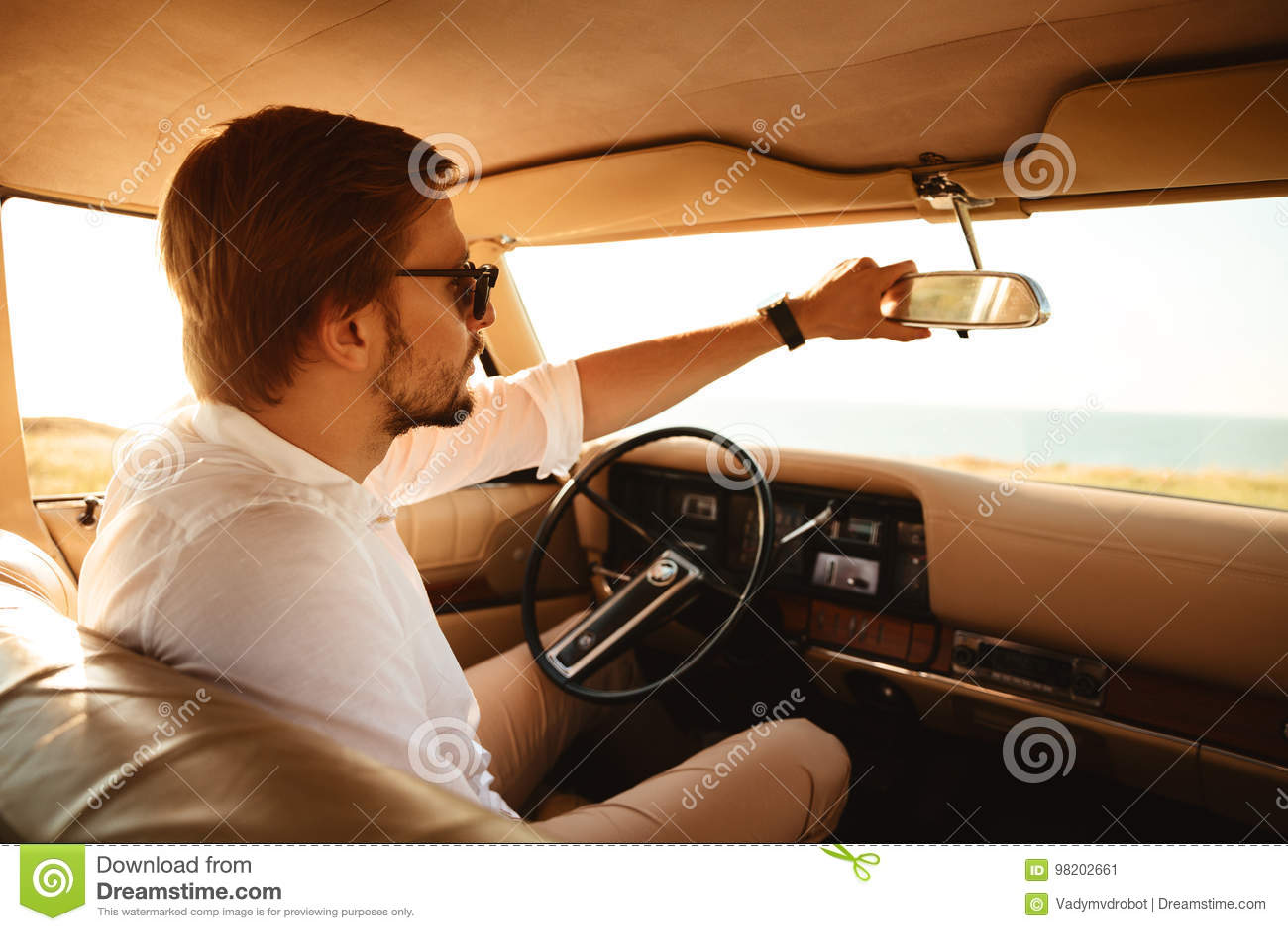 Ung stilig man i solglasögon som sitter inom hans bil