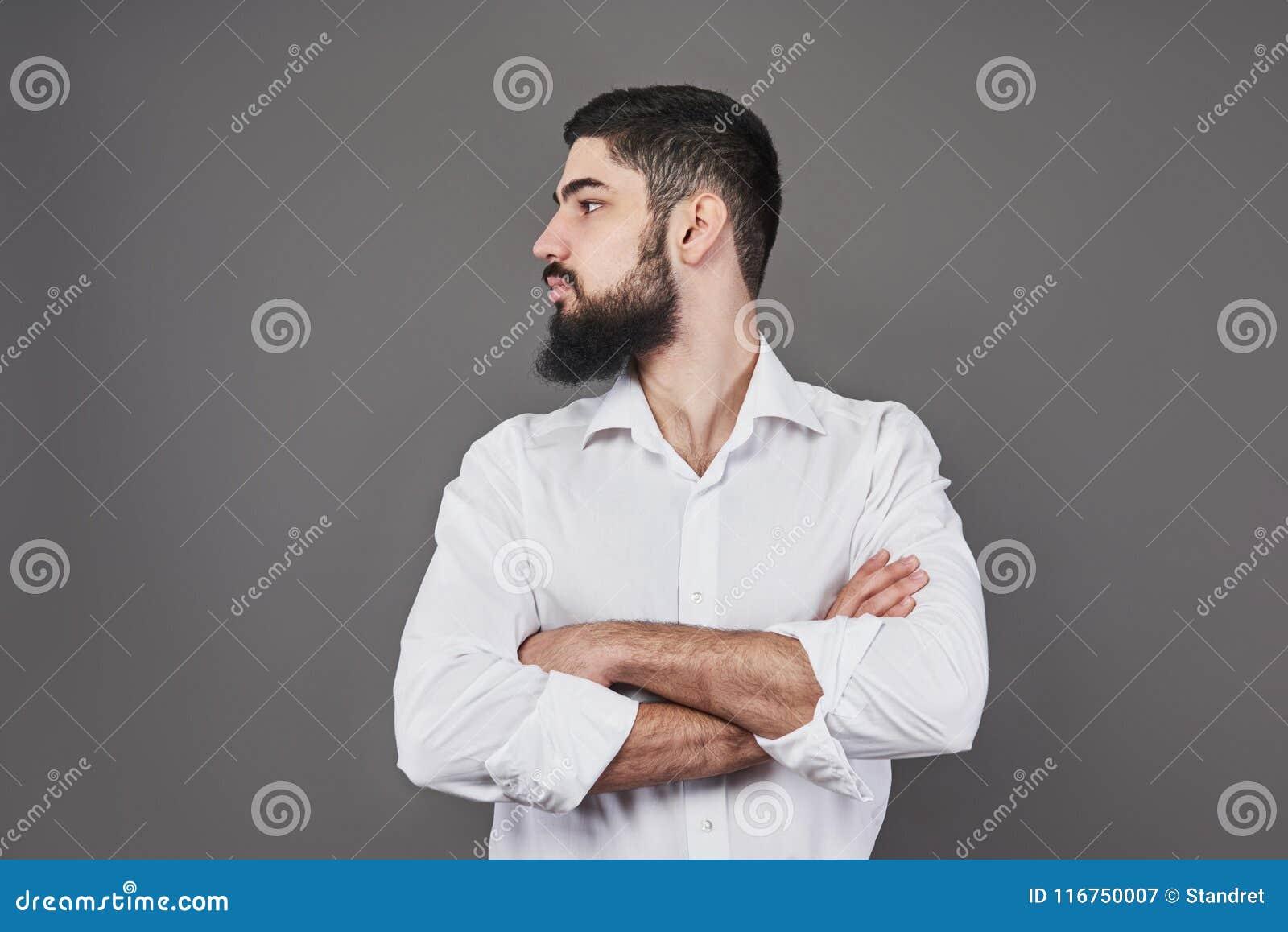 Ung stilig man med en skäggbenägenhet mot den gråa väggen med korsade armar