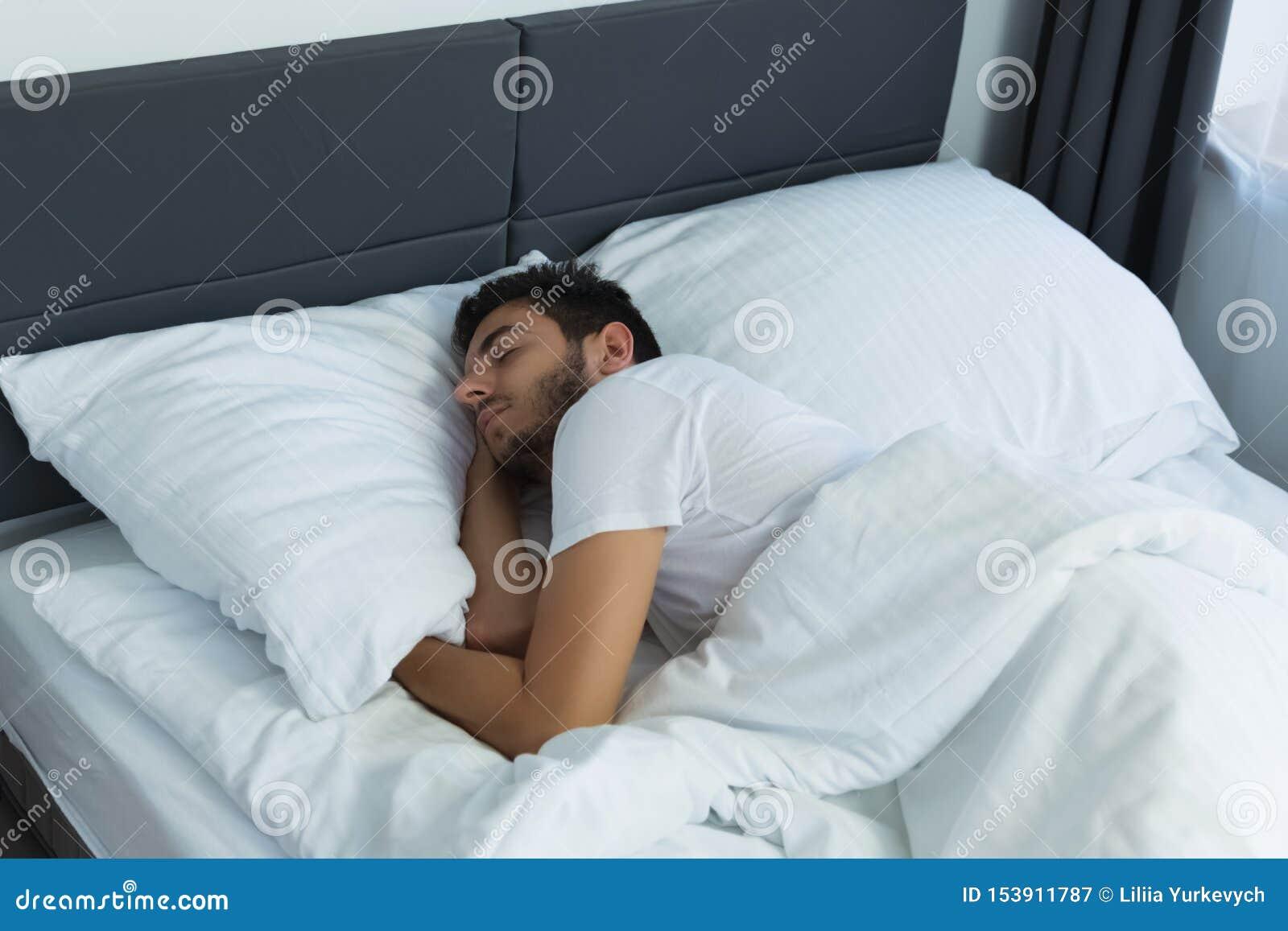 Ung stilig man som sover i hans säng