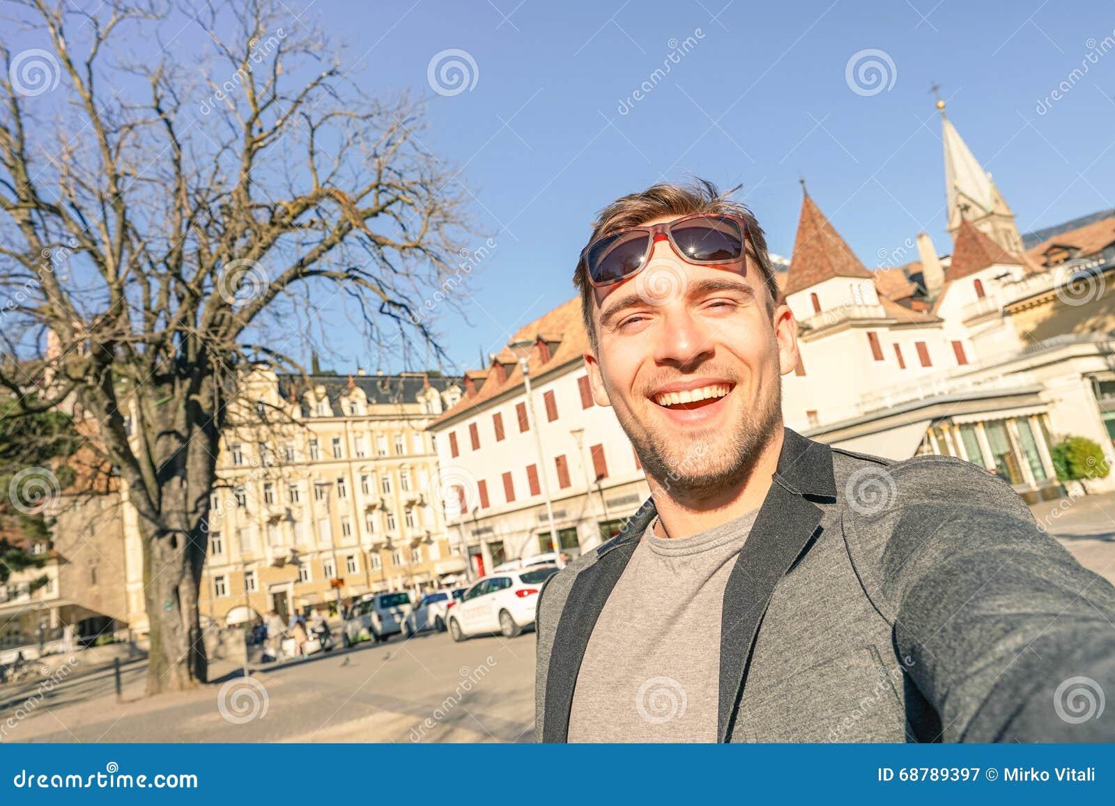 Ung stilig man som tar selfie på Meran den gamla staden södra Tyrol