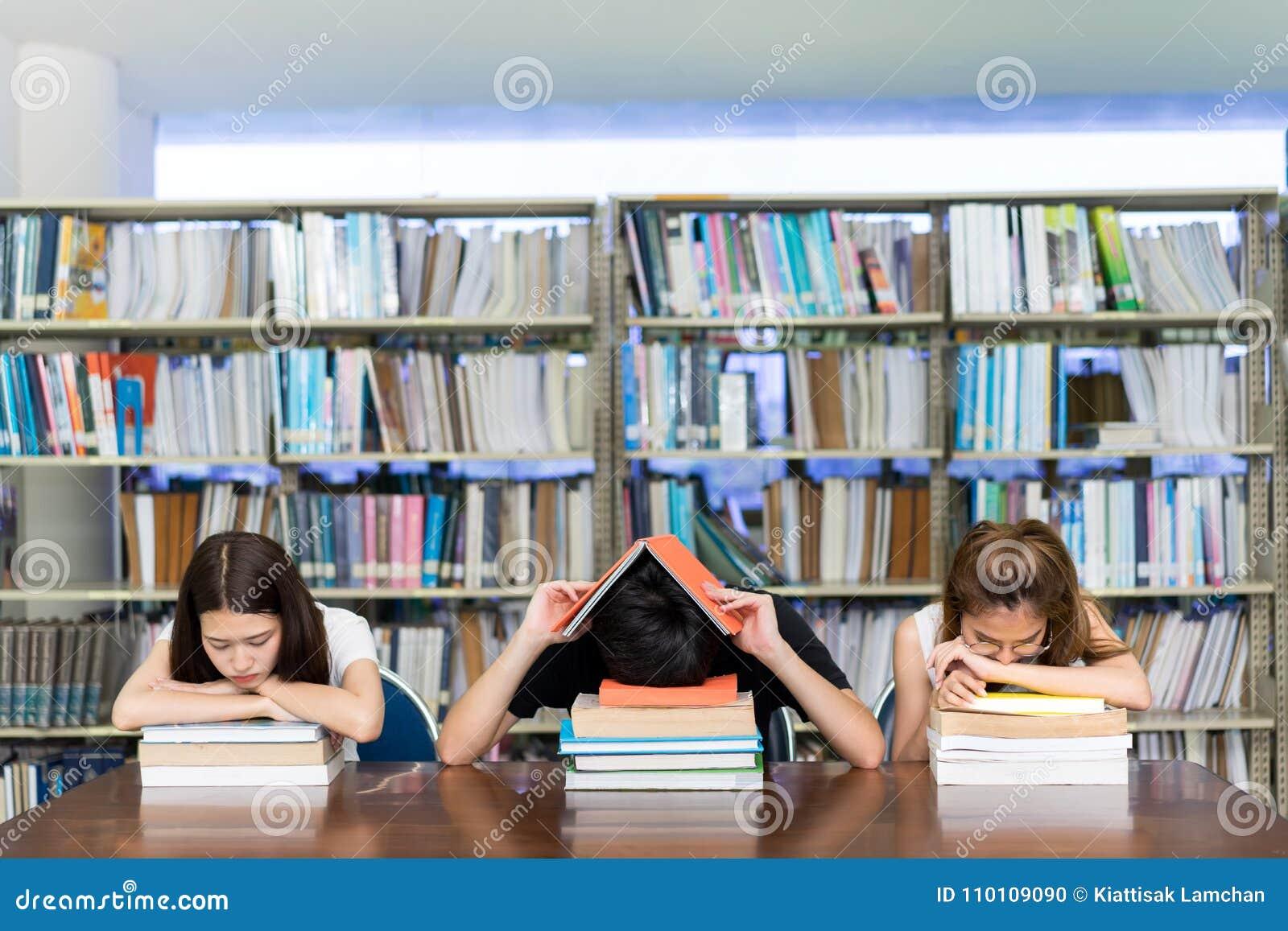Ung student allvarliga Group Reading Book, hård examen, frågesport, prov som sover huvudvärkbekymmer i universitet för klassrumut