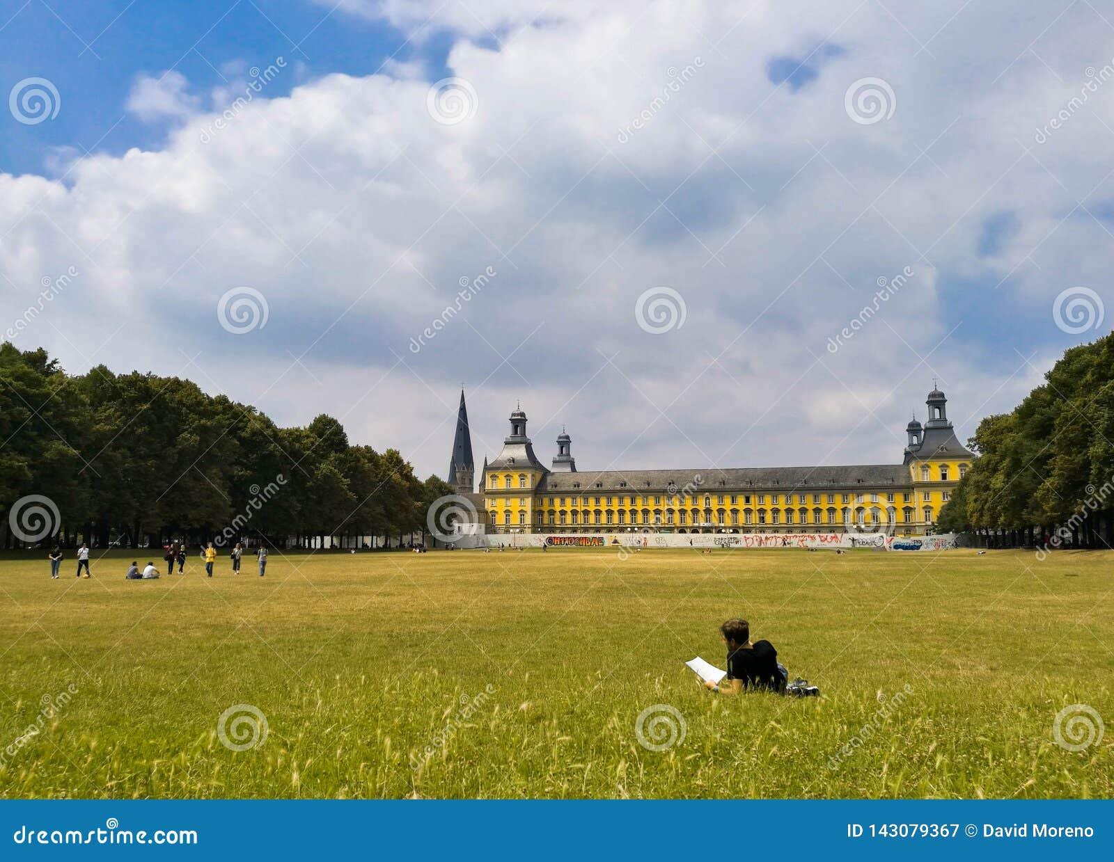 Ung student som vilar på gräsläsningen en bok