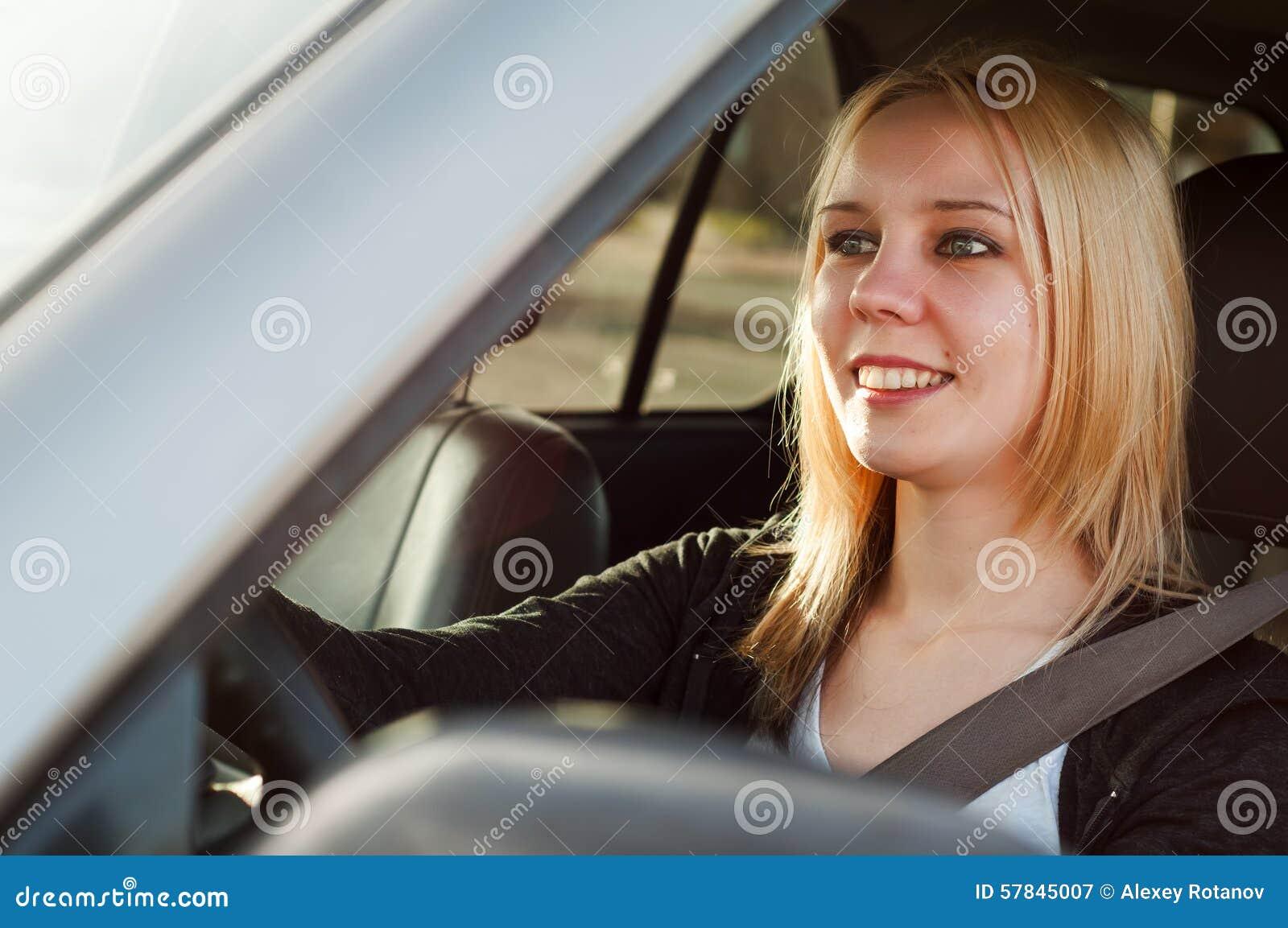 Ung studentflicka som kör en bil
