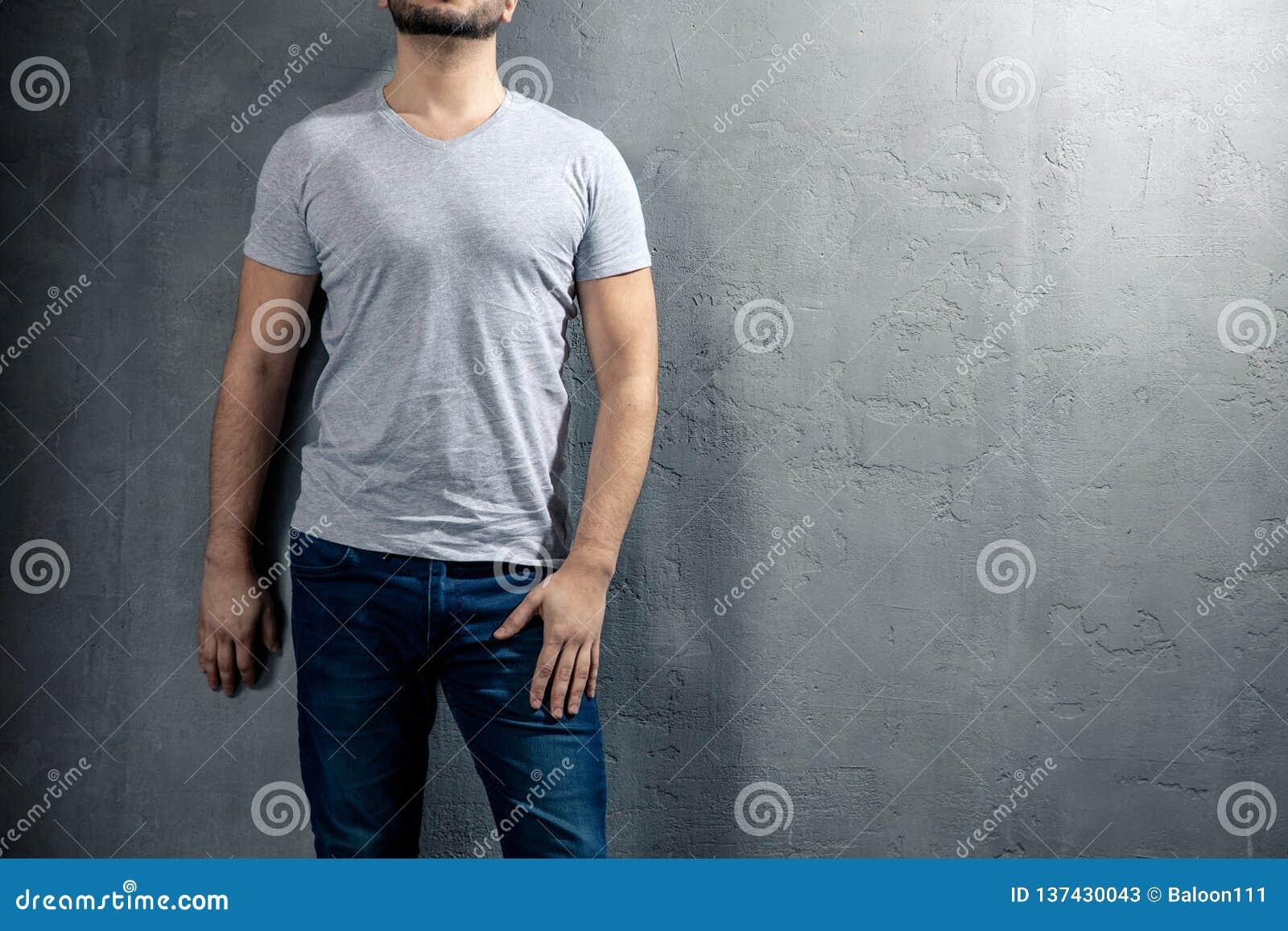 Ung sund man med den gråa T-tröja på konkret bakgrund med copyspace för din text