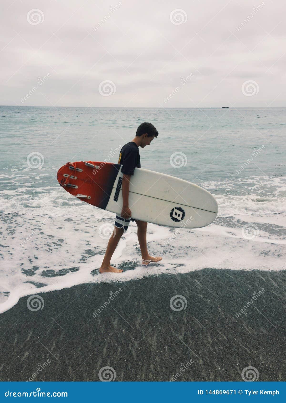 Ung surfare som går på stranden