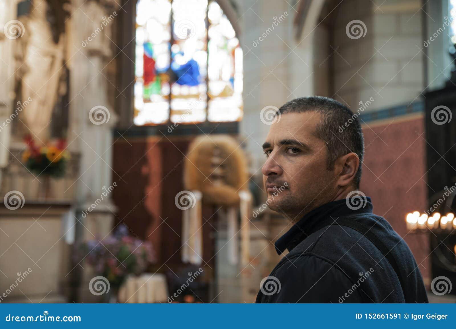Ung svart-haired man i för en katolsk kyrka sikt entusiastiskt