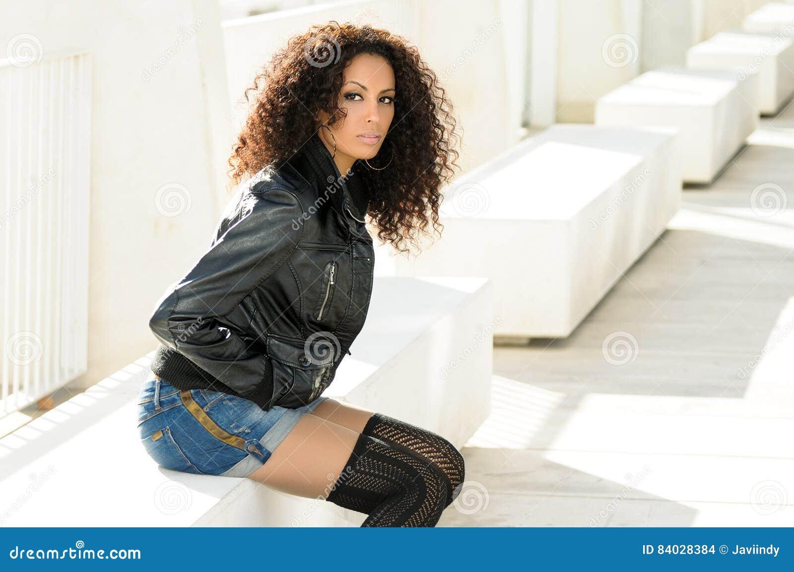 Ung svart kvinna, afro frisyr, i stads- bakgrund
